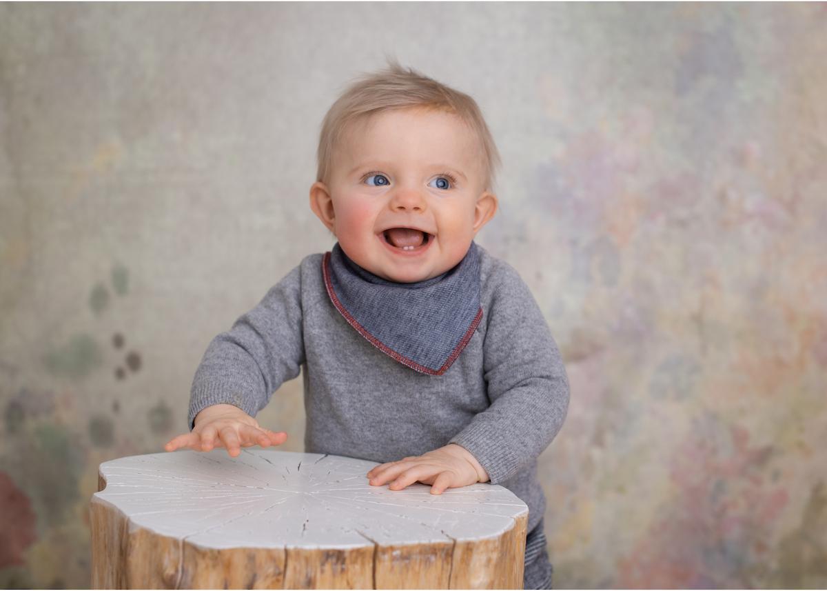 Babyfotografering med glad 9-månaders bebis. Studiofotografering med bakgrund, stubbe att stå vid. barnfotograf Blicka Studio